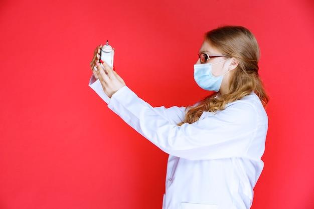 Arzt mit gesichtsmaske, der versucht, den wecker zu stellen.