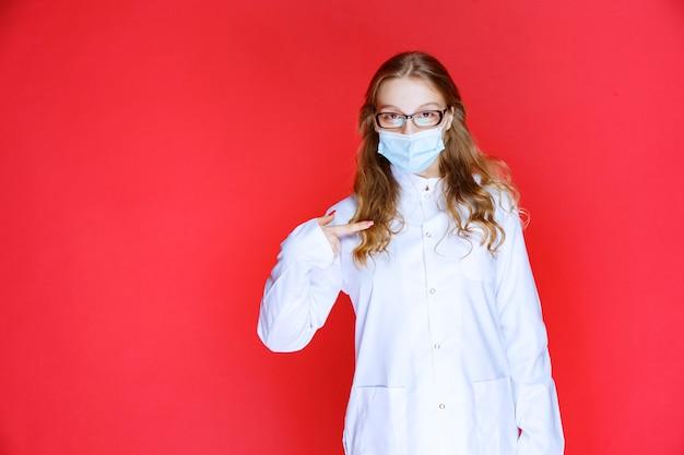 Arzt mit gesichtsmaske, die auf sich selbst zeigt.