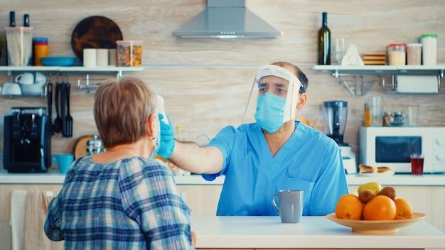 Arzt mit gesichtsmaske, die die temperatur der älteren frau mit dem waffenthermometer während des hausbesuchs überprüft. sozialarbeiter, der während der covid-19-kampagne gefährdete personen besucht, um die verbreitung von krankheiten zu verhindern