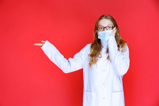 Arzt mit gesichtsmaske nach links zeigend.