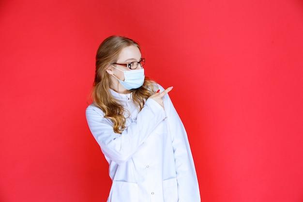 Arzt mit gesichtsmaske nach rechts zeigend.