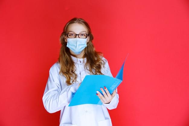 Arzt mit gesichtsmaske öffnet und überprüft die krankengeschichte des patienten.