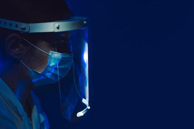 Arzt mit gesichtsschutz und maske auf dunkelblauem hintergrund