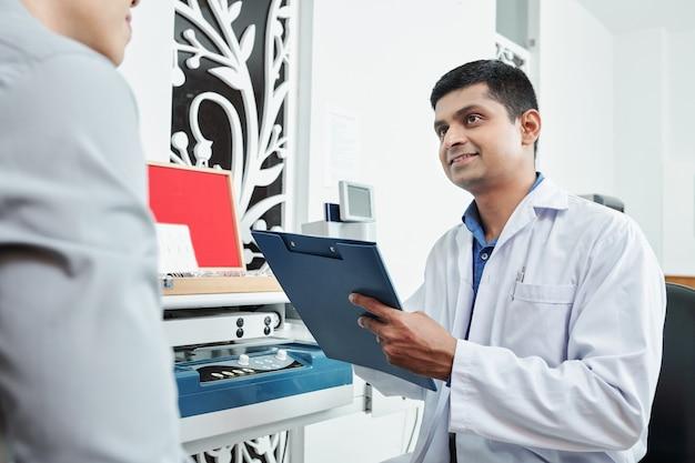 Arzt mit gesundheitskarte im büro