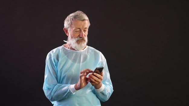Arzt mit grauen haaren in einem operationsanzug benutzt ein smartphone in einem dunklen raum.