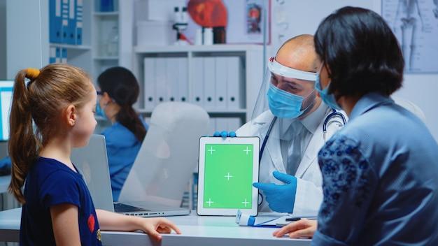 Arzt mit greenscreen-tablet in der arztpraxis während covid-19. gesundheitsspezialist mit chroma-key-notebook isolierter mockup-ersatzbildschirm. einfaches tastendes medizinisches medizinisches thema.