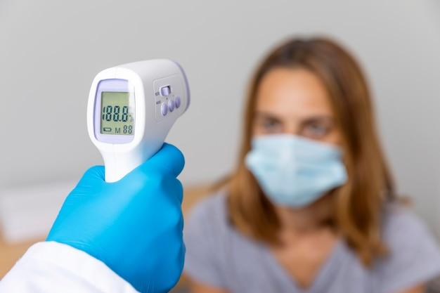 Arzt mit handschuhen, der die temperatur des patienten mit einem thermometer überprüft