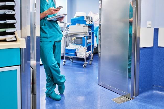 Arzt mit handy in einem krankenhaus, das sich an eine tür eines raumes mit medizinischer ausrüstung lehnt