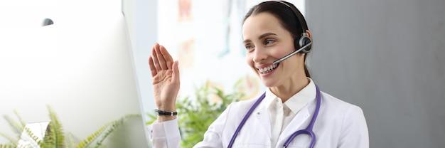 Arzt mit kopfhörern und mikrofon winkt mit der hand am computerbildschirm