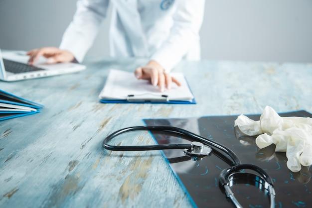 Arzt mit medizinischer ausrüstung auf dem schreibtisch