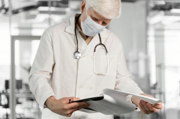 Arzt mit medizinischer maske, der seine notizen überprüft
