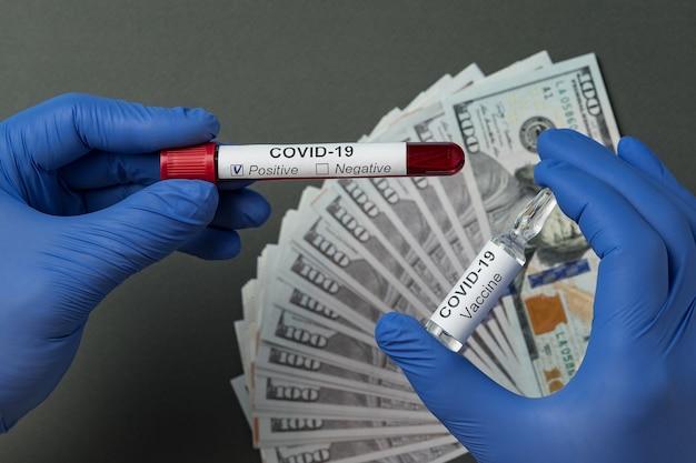 Arzt mit positivem bluttest auf coronavirus und fläschchen mit impfstoff gegen covid-19. preis für heilung, medizinische handschuhe