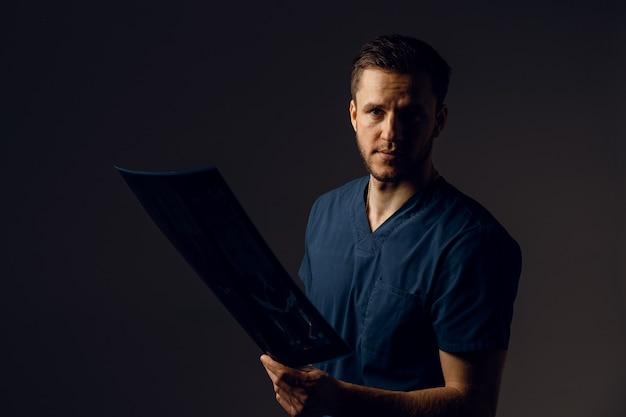 Arzt mit röntgenaufnahme eines kranken patienten mit coronavirus covid-19. computertomographie. chirurg in der medizinischen robe, die bild des scans betrachtet. mri für die diagnose der gesundheit