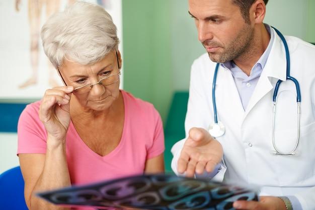 Arzt mit seinem älteren patienten, der den medizinischen test analysiert