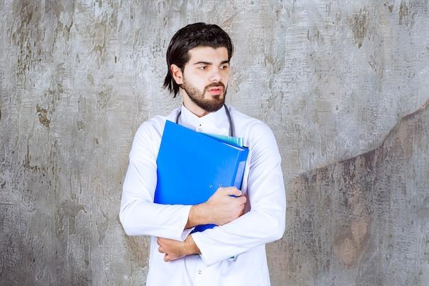 Arzt mit stethoskop, der mehrere bunte meldeordner hält und verwirrt oder unsicher aussieht