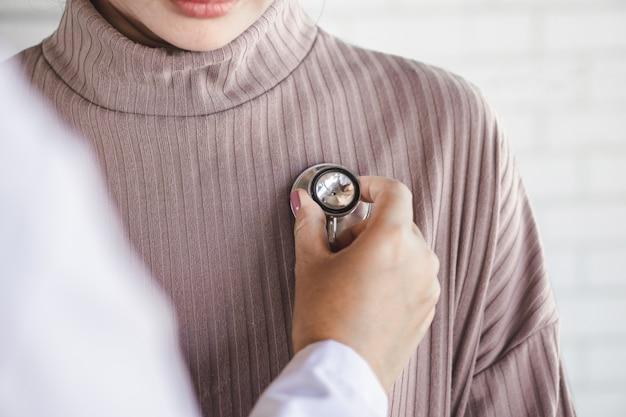 Arzt mit stethoskop untersucht patientenherzschlag