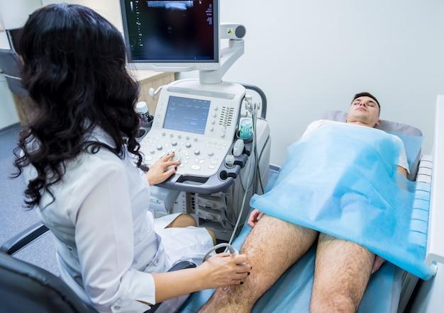 Arzt mit ultraschallgerät, das verletztes knie untersucht.