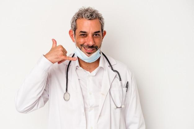 Arzt mittleren alters, der eine maske für viren trägt, die auf weißem hintergrund isoliert ist und eine handy-anrufgeste mit den fingern zeigt.
