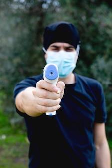 Arzt nimmt temperatur mit infrarot-thermometer