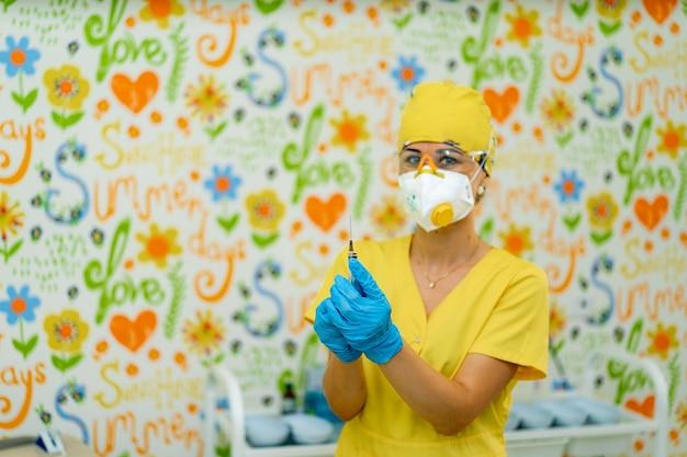 Arzt oder krankenschwester hand in blauen handschuhen mit spritze mit impfstoff für ein baby oder einen erwachsenen. medizin- und drogenkonzept.