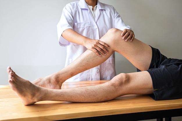 Arzt oder physiotherapeut, der die behandlung eines verletzten beins eines männlichen sportlers untersucht und die schmerzen der rehabilitationstherapie in der klinik durchführt.
