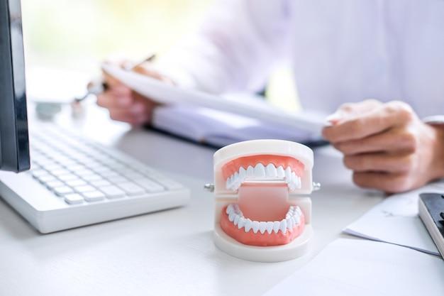 Arzt oder zahnarzt schreiben einen bericht, der mit zahnröntgenfilm, modell und ausrüstung arbeitet