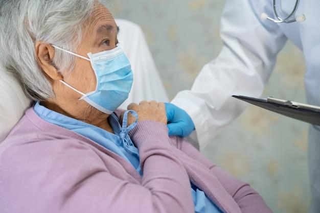 Arzt prüft asiatische ältere patientin, die eine gesichtsmaske trägt, um covid-19 coronavirus zu schützen.