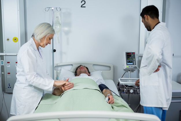 Arzt prüft den puls des patienten