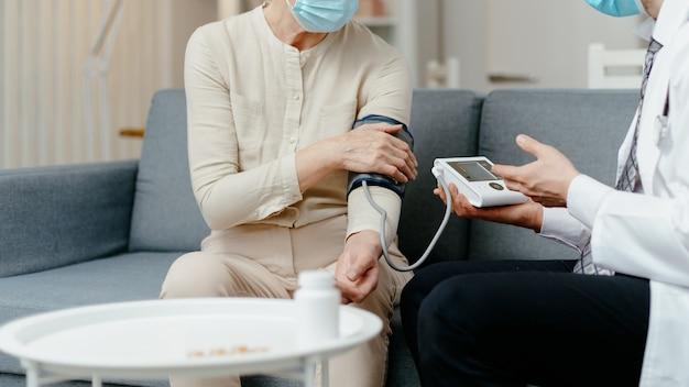 Arzt schaut während eines besuchs beim patienten auf den monitor des blutdruckmessgeräts