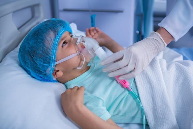 Arzt setzt eine sauerstoffmaske auf den patienten in der station