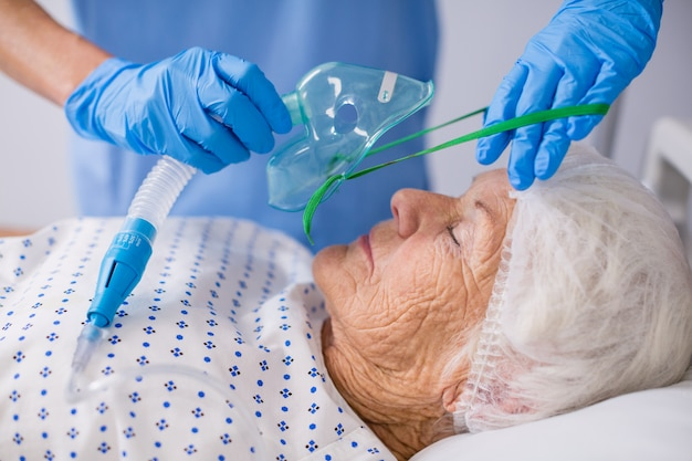 Arzt setzt eine sauerstoffmaske auf den patienten