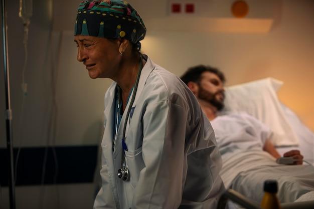 Arzt sieht traurig neben einem patienten aus
