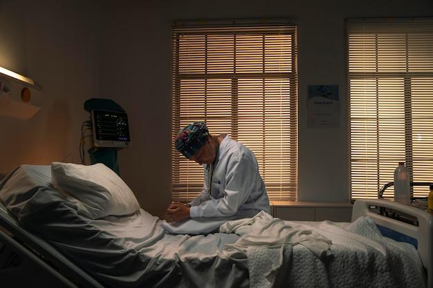 Arzt sitzt auf einem krankenhausbett und ist traurig