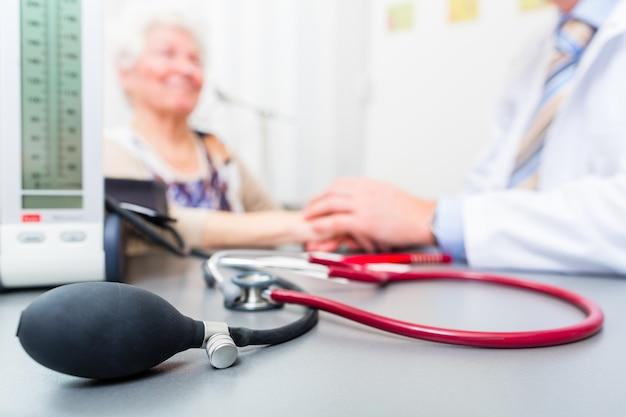 Arzt sitzt mit rentner in der sprechstunde am schreibtisch