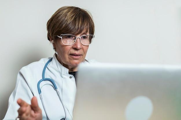 Arzt spricht mit dem patienten per videoanruf auf dem laptop und gibt medizinischen rat. telemedizin termin