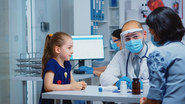 Arzt spricht mit kind, das während des coronavirus eine schutzmaske trägt. kinderarzt, facharzt für medizin, der gesundheitsdienste, beratung, behandlung, untersuchung im krankenhausschrank anbietet.