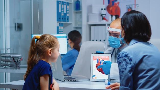 Arzt spricht mit patienten während des coronavirus über herzfunktionen mit tablet. kinderarzt in schutzhandschuhen und maske, die beratung für medizinische gesundheitsdienste in der klinik bietet