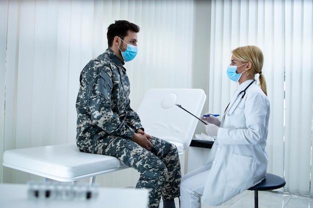 Arzt spricht mit soldat in uniform im krankenhaus während des koronavirus.