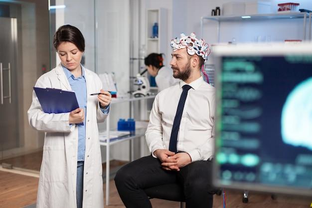 Arzt spricht über krankheitssymptome während der untersuchungen mit einem high-tech-headset zum scannen von gehirnwellen. forscher, der den gesundheitszustand des patienten, die gehirnfunktionen und das nervensystem analysiert.