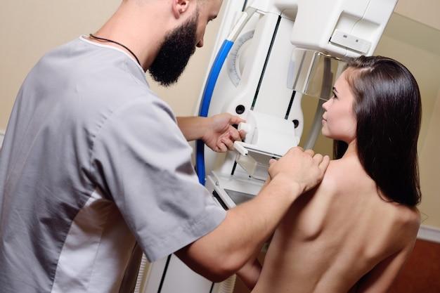 Arzt stehend assistierender patient, der sich einer mammographie-röntgenuntersuchung unterzieht. prävention von brustkrebs