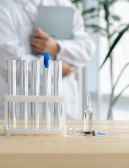 Arzt steht in der nähe des tisches mit reagenzgläsern, ampulle und spritze, konzept der globalen impfung.