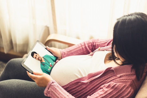 Arzt telemedizin service online-video mit schwangeren frau für die schwangerschaftsvorsorge