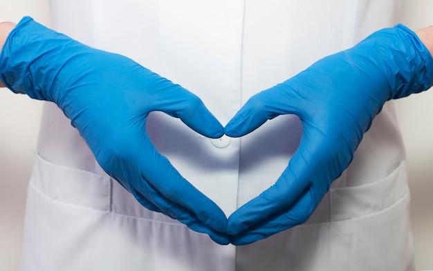 Arzt übergibt handschuhe in form vor dem hintergrund seines körpers in form einer herznahaufnahme