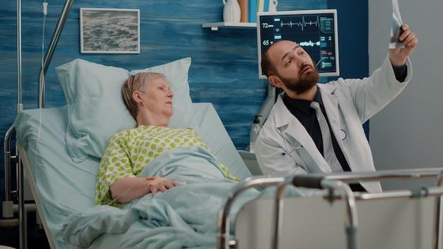 Arzt und ältere frau im bett, die röntgenaufnahme betrachten