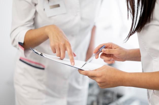 Arzt und assistent überprüfen die medizinische form