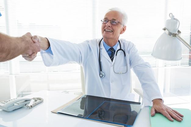 Arzt und chirurg geben sich die hand