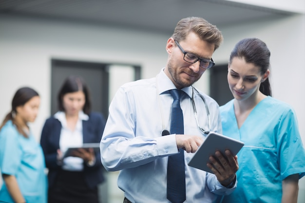Arzt und krankenschwester diskutieren über digitales tablet
