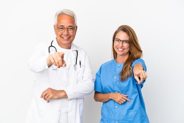 Arzt und krankenschwester mittleren alters, die auf weißem hintergrund isoliert sind, zeigen mit einem selbstbewussten ausdruck mit dem finger auf sie