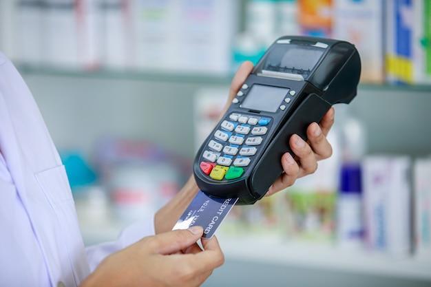 Arzt und kreditkartenautomat halten hand