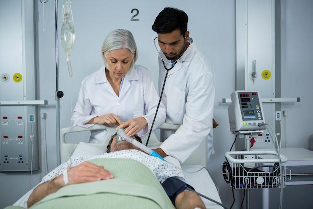 Arzt und untersuchung eines patienten mit stethoskop und platzieren einer sauerstoffmaske